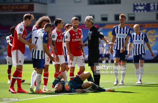 Arsenal's German goalkeeper Bernd Leno lays injured during the English Premier League football match between Brighton and Hove Albion and Arsenal at...