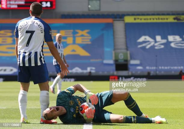 Arsenal's German goalkeeper Bernd Leno lies on the ground next to Brighton's French striker Neal Maupay during the English Premier League football...