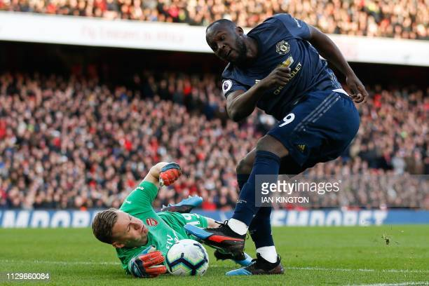 Arsenal's German goalkeeper Bernd Leno manages to block and save the shot from Manchester United's Belgian forward Romelu Lukaku during the English...