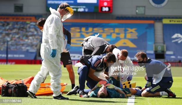 Arsenal's German goalkeeper Bernd Leno receives treatment after being injured during the English Premier League football match between Brighton and...