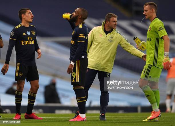 Arsenal's German goalkeeper Bernd Leno takes a drinks break with teammates during the English Premier League football match between Manchester City...