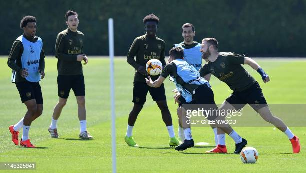 Arsenal's German midfielder Mesut Ozil and Arsenal's Armenian midfielder Henrikh Mkhitaryan watch as Arsenal's German defender Shkodran Mustafi vies...