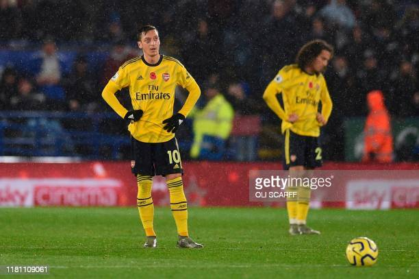 Arsenal's German midfielder Mesut Ozil and Arsenal's French midfielder Matteo Guendouzi reacts as they wait to restart after Leicester City score the...