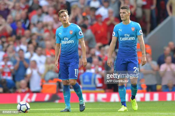 Arsenal's German midfielder Mesut Ozil and Arsenal's Swiss midfielder Granit Xhaka react after conceding their fourth goal during the English Premier...