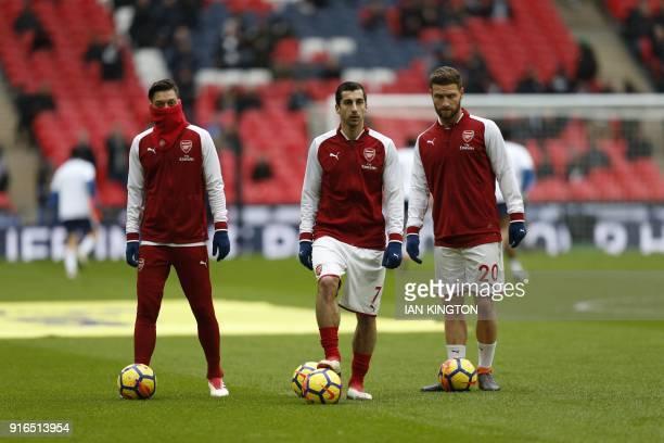 Arsenal's German midfielder Mesut Ozil Arsenal's Armenian midfielder Henrikh Mkhitaryan and Arsenal's German defender Shkodran Mustafi warm up for...