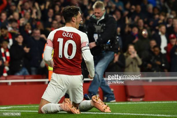 Arsenal's German midfielder Mesut Ozil celebrates after scoring their first goal during the English Premier League football match between Arsenal and...