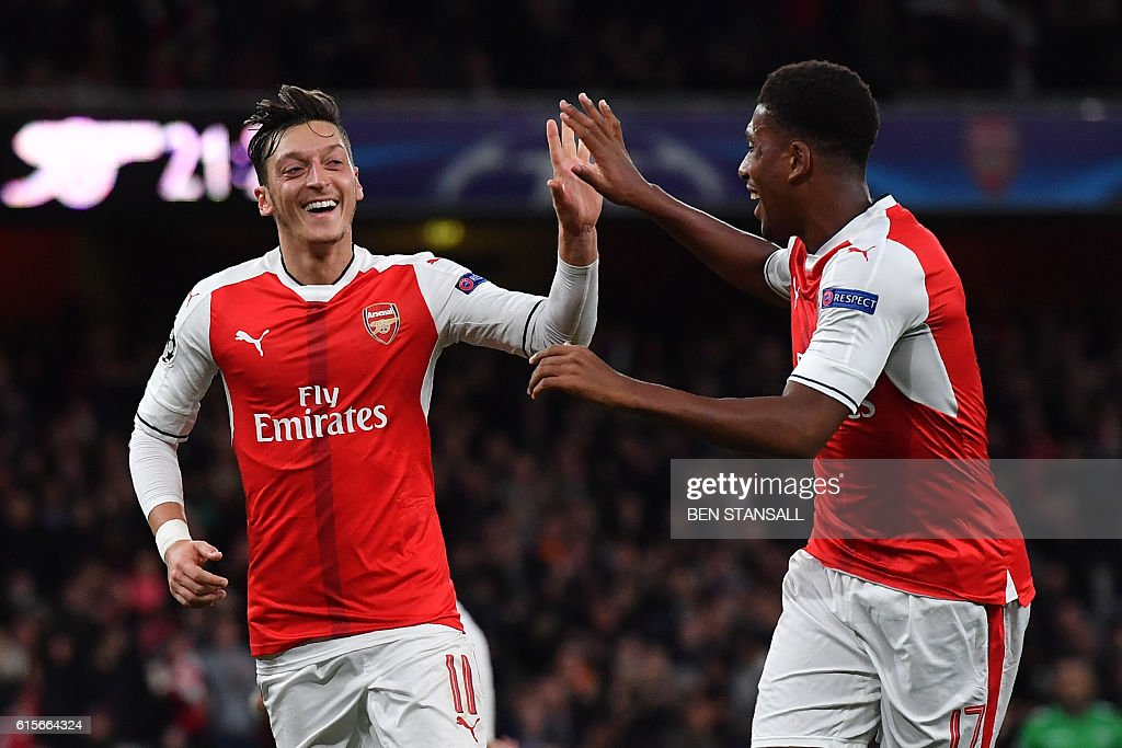 TOPSHOT - Arsenal's German midfielder Mesut Ozil (O) celebrates scoring his team's sixth goal with Arsenal's Nigerian striker Alex Iwobi during the UEFA Champions League Group A football match between Arsenal and Ludogorets Razgrad at The Emirates Stadium in London on October 19, 2016. / AFP / BEN