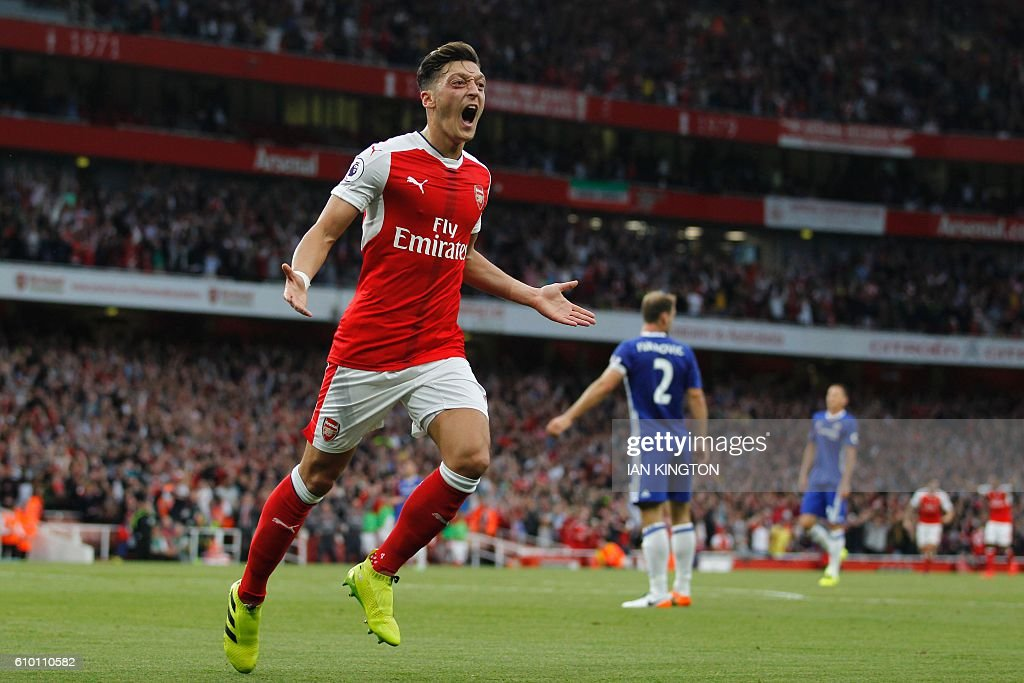 Arsenal's German midfielder Mesut Ozil celebrates scoring their third goal during the English Premier League football match between Arsenal and Chelsea at The Emirates stadium in London, on September 24, 2016. / AFP / IKIMAGES / Ian Kington / RESTRICTED TO EDITORIAL USE. No use with unauthorized audio, video, data, fixture lists, club/league logos or 'live' services. Online in-match use limited to 45 images, no video emulation. No use in betting, games or single club/league/player publications.