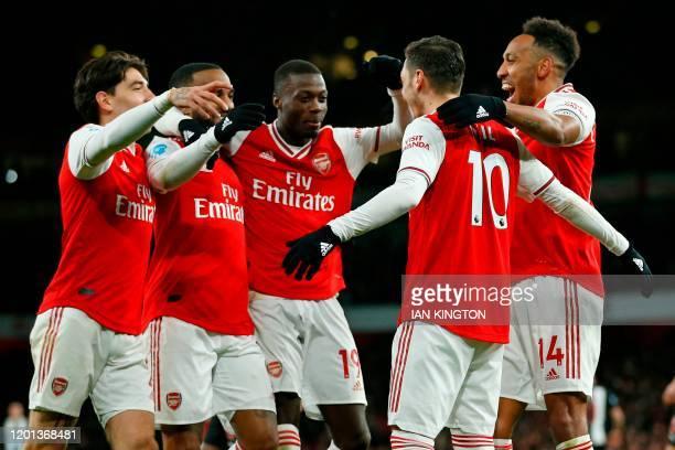 Arsenal's German midfielder Mesut Ozil celebrates with teammates after scoring their third goal during the English Premier League football match...