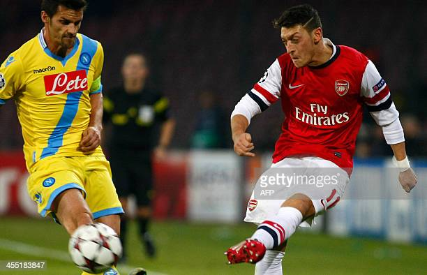 Arsenal's German midfielder Mesut Ozil fights for the ball with Napoli's midfielder Christian Maggio during the UEFA Champion's League group F...