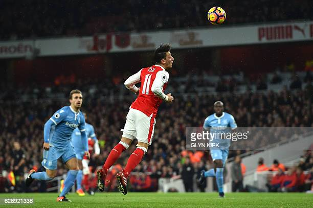 Arsenal's German midfielder Mesut Ozil heads the ball to score their second goal during the English Premier League football match between Arsenal and...