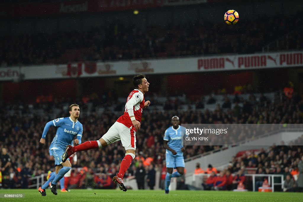 Arsenal's German midfielder Mesut Ozil (C) heads the ball to score their second goal during the English Premier League football match between Arsenal and Stoke City at the Emirates Stadium in London on December 10, 2016. / AFP / Glyn KIRK / RESTRICTED TO EDITORIAL USE. No use with unauthorized audio, video, data, fixture lists, club/league logos or 'live' services. Online in-match use limited to 75 images, no video emulation. No use in betting, games or single club/league/player publications. /