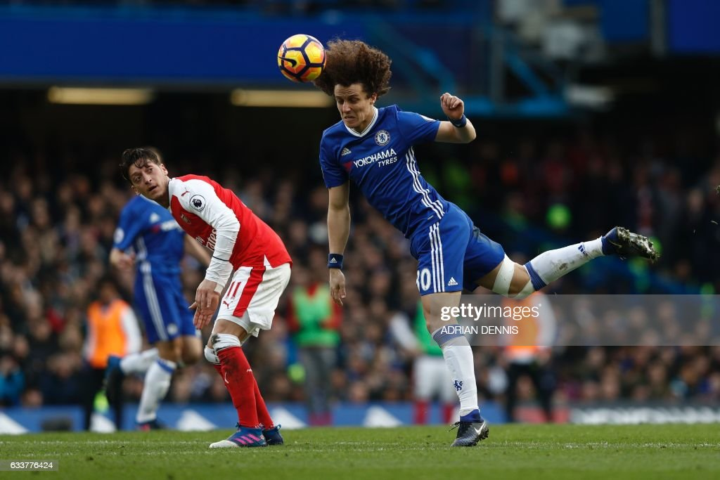 TOPSHOT - Arsenal's German midfielder Mesut Ozil (L) looks on as Chelsea's Brazilian defender David Luiz (R) heads the ball during the English Premier League football match between Chelsea and Arsenal at Stamford Bridge in London on February 4, 2017. / AFP / Adrian DENNIS / RESTRICTED TO EDITORIAL USE. No use with unauthorized audio, video, data, fixture lists, club/league logos or 'live' services. Online in-match use limited to 75 images, no video emulation. No use in betting, games or single club/league/player publications. /