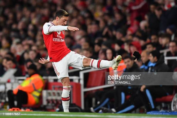 Arsenal's German midfielder Mesut Ozil reacts to his substitution by kicking his gloves along the touchline during the English Premier League...