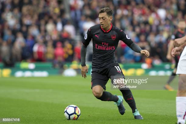 Arsenal's German midfielder Mesut Ozil runs with the ball during the English Premier League football match between Stoke City and Arsenal at the...