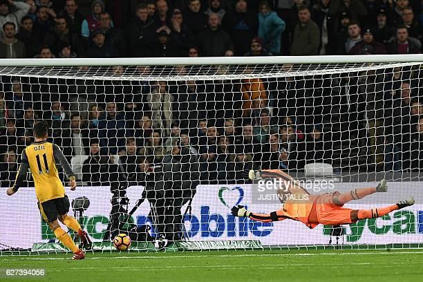 Arsenal's German midfielder Mesut Ozil scores the opening goal past West Ham United's Irish goalkeeper Darren Randolph during the English Premier...