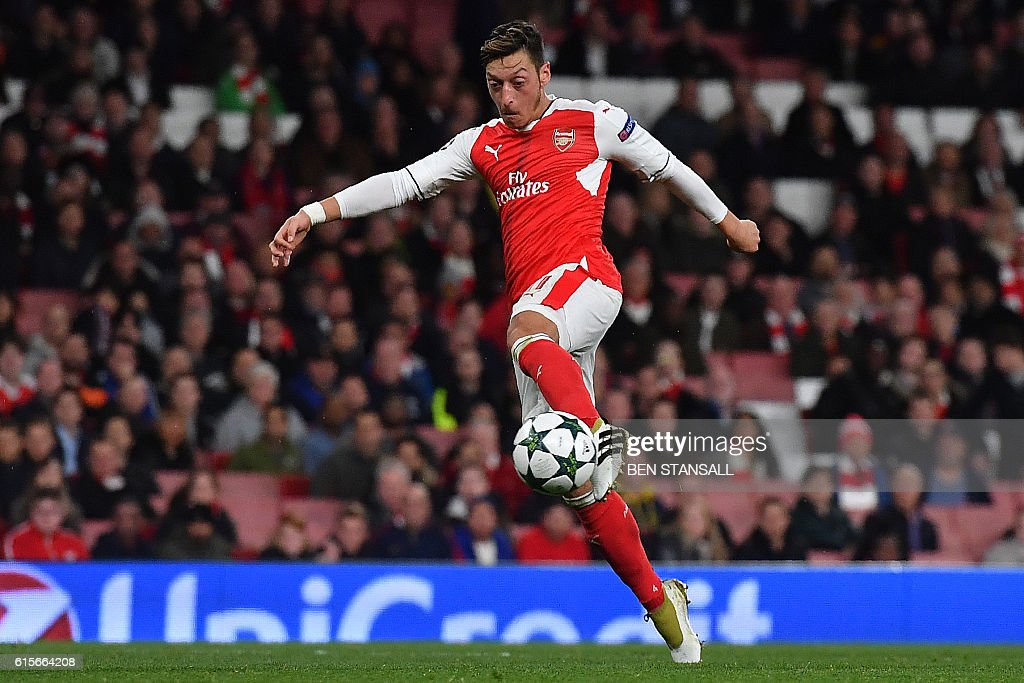 Arsenal's German midfielder Mesut Ozil shoots to score his hat trick, and his teams sixth goal, during the UEFA Champions League Group A football match between Arsenal and Ludogorets Razgrad at The Emirates Stadium in London on October 19, 2016. / AFP / BEN