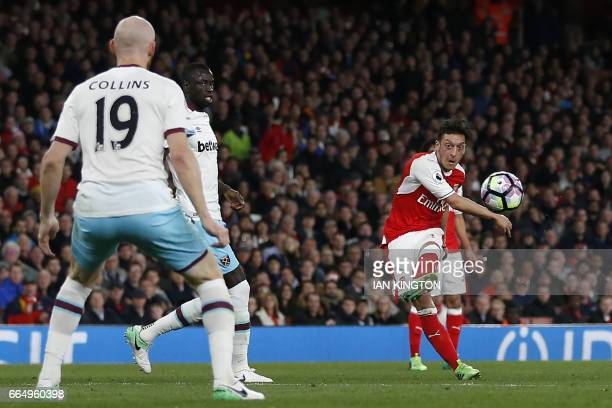 Arsenal's German midfielder Mesut Ozil shoots to score the opening goal of the English Premier League football match between Arsenal and West Ham...