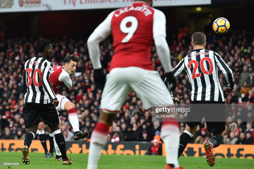 Arsenal's German midfielder Mesut Ozil (2nd L) shoots to score the opening goal of the English Premier League football match between Arsenal and Newcastle United at the Emirates Stadium in London on December 16, 2017. / AFP PHOTO / Glyn KIRK / RESTRICTED TO EDITORIAL USE. No use with unauthorized audio, video, data, fixture lists, club/league logos or 'live' services. Online in-match use limited to 75 images, no video emulation. No use in betting, games or single club/league/player publications. /