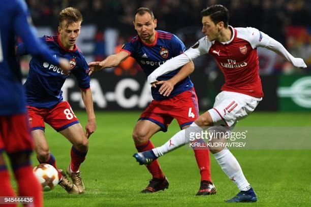 Arsenal's German midfielder Mesut Ozil vies CSKA Moscow's Russian defender Sergei Ignashevich and CSKA Moscow's Russian midfielder Konstantin...