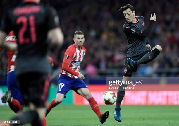 Arsenal's German midfielder Mesut Ozil vies with Atletico Madrid's French defender Lucas Hernandez during the UEFA Europa League semi-final second...