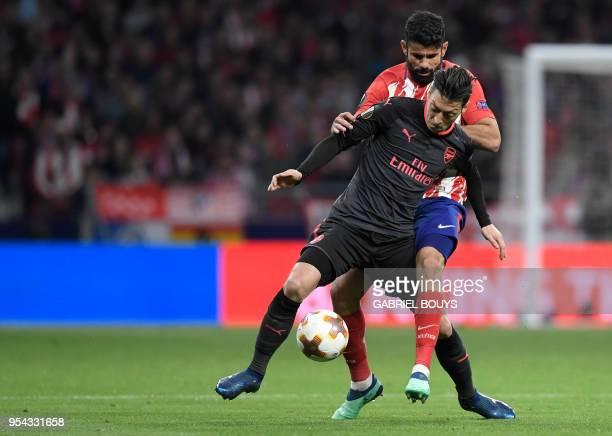 Arsenal's German midfielder Mesut Ozil vies with Atletico Madrid's Spanish forward Diego Costa during the UEFA Europa League semi-final second leg...