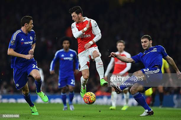 TOPSHOT Arsenal's German midfielder Mesut Ozil vies with Chelsea's Serbian midfielder Nemanja Matic and Chelsea's Serbian defender Branislav Ivanovic...