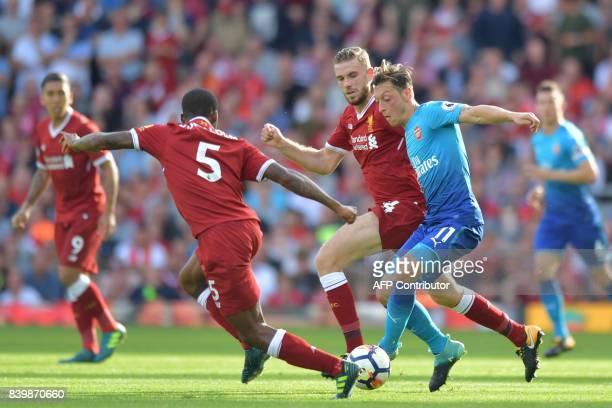 Arsenal's German midfielder Mesut Ozil vies with Liverpool's English midfielder Jordan Henderson and Liverpool's Dutch midfielder Georginio Wijnaldum...