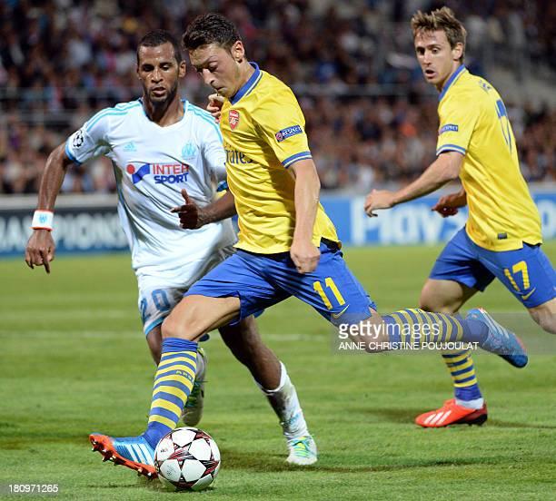 Arsenal's German midfielder Mesut Ozil vies with Marseille's Togolese midfielder JacquesAlaixys Romao on September 18 2013 at the Velodrome stadium...