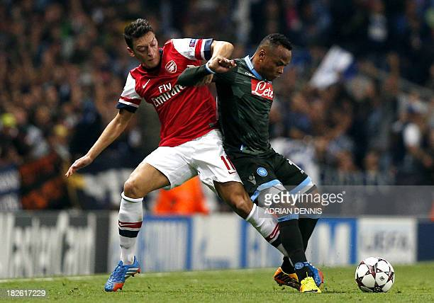 Arsenal's German midfielder Mesut Ozil vies with SSC Napoli's Colombian midfielder Camilo Zuniga during their UEFA Champions League Group F football...