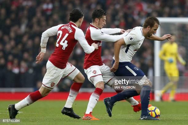 Arsenal's German midfielder Mesut Ozil vies with Tottenham Hotspur's English striker Harry Kane during the English Premier League football match...