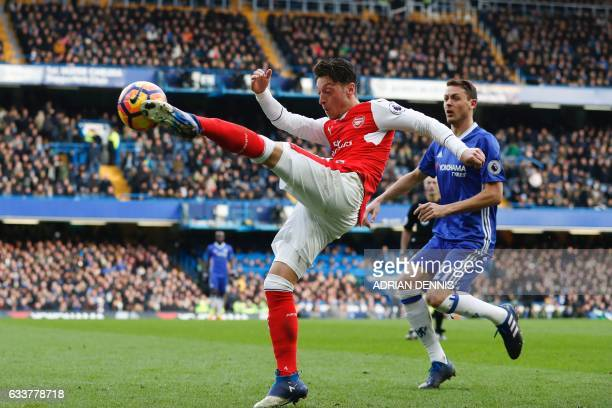 TOPSHOT Arsenal's German midfielder Mesut Ozil vollies the ball during the English Premier League football match between Chelsea and Arsenal at...
