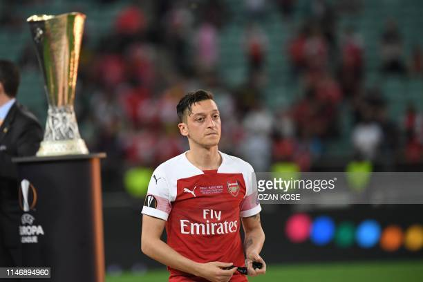 Arsenal's German midfielder Mesut Ozil walks past the trophy after losing the UEFA Europa League final football match between Chelsea FC and Arsenal...