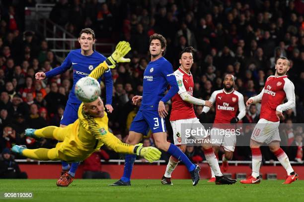 Arsenal's German midfielder Mesut Ozil watches as he misses a shot at goal as Chelsea's Argentinian goalkeeper Willy Caballero dives during the...