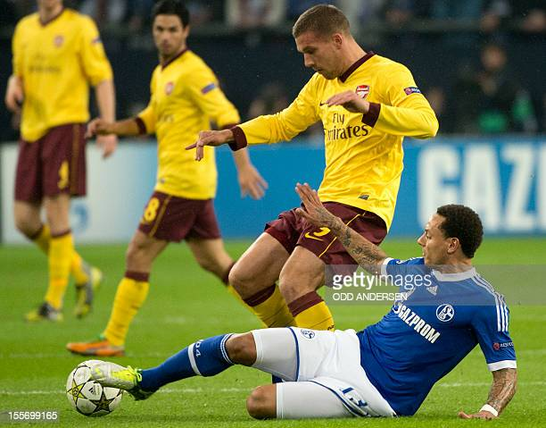 Arsenal´s German striker Lukas Podolski and Schalke's US midfielder Jermaine Jones vie for the ball during the UEFA Champions league group B football...
