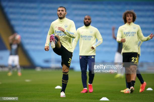Arsenal's Germanborn Bosnian defender Sead Kolasinac and Arsenal's French midfielder Matteo Guendouzi warm up in front of empty stands ahead of the...