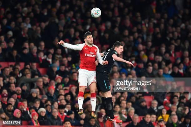 Arsenal's Germanborn Bosnian defender Sead Kolasinac jumps against West Ham United's Irish defender Declan Rice during the English League Cup...
