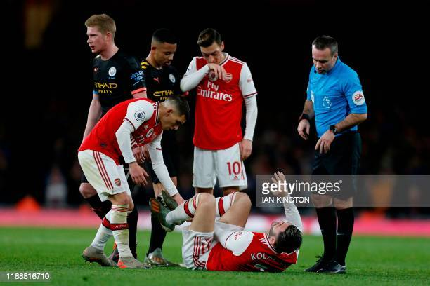 Arsenal's Germanborn Bosnian defender Sead Kolasinac reacts after picking up an injury during the English Premier League football match between...