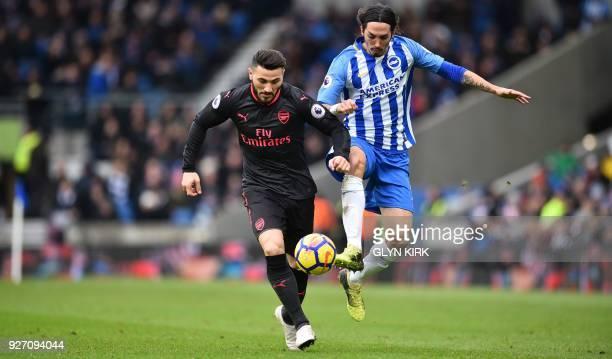 Arsenal's Germanborn Bosnian defender Sead Kolasinac vies with Brighton's Argentineborn Italian defender Ezequiel Schelotto during the English...