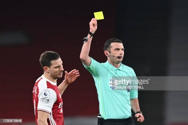 Arsenal's German-born Portuguese defender Cedric Soares gets a yellow card from referee Michael Oliver during the English Premier League football...