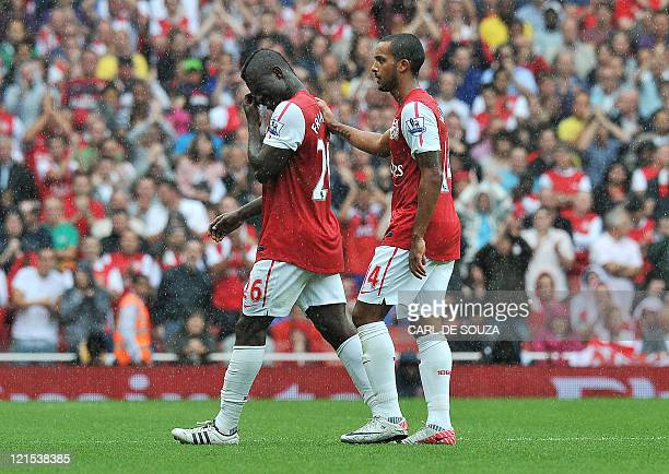 Arsenal's Ghanaian/English midfielder Emmanuel Frimpong is consoled by teammate Theo Walcott as he walks off the pitch after receiving a red card...
