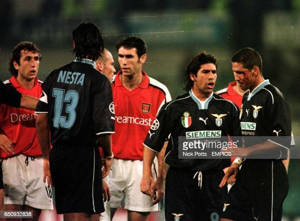 Arsenal's Gilles Grimandi looks on as Lazio's Diego Simeone seeks medical help for a cut eyebrow that was allegedly caused by a Grimandi punch