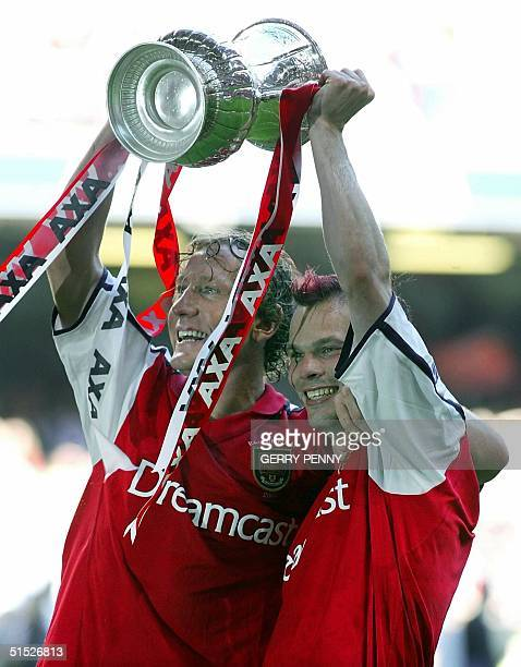 Arsenal's goal scorers Ray Parlour and Freddie Ljungberg celebrate 04 May 2002 with the FA Cup after beating Chelsea 20 at The Millennium Stadium in...