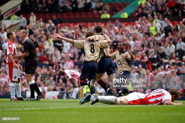 Arsenal's goalscorer Fredrik Ljungberg celebrates scoring the opening goal against Sheffield United with teammate Francis Jeffers as Referee Graham...