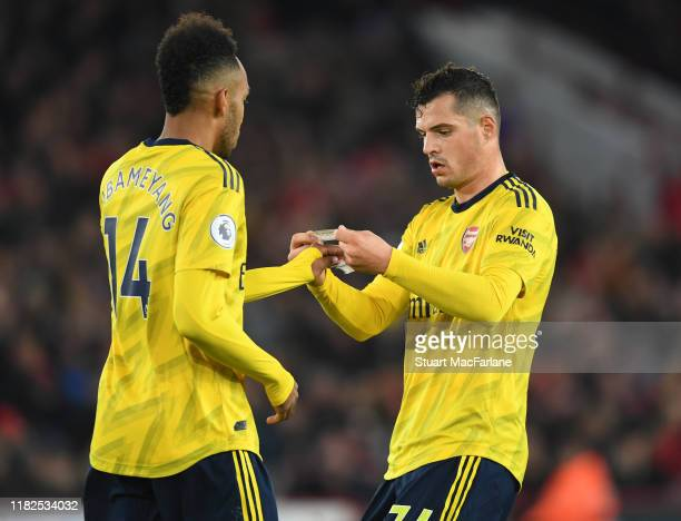 Arsenal's Granit Xhaka gives Pierre-Emerick Aubameyang the captains armband during the Premier League match between Sheffield United and Arsenal FC...