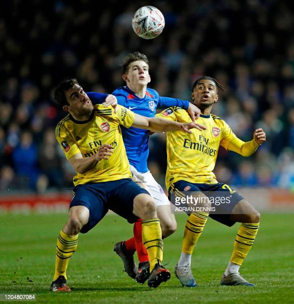 Arsenal's Greek defender Sokratis Papastathopoulos and Arsenal's English midfielder Reiss Nelson tangle with Portsmouth's English defender Steve...