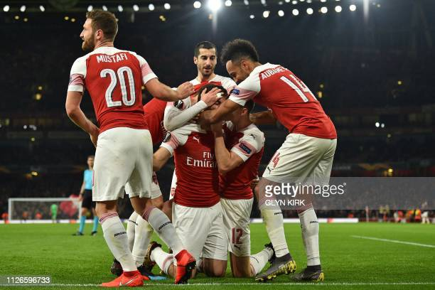 Arsenal's Greek defender Sokratis Papastathopoulos celebrates with teammates after scoring their third goal during the UEFA Europa League round of 32...