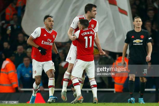 Arsenal's Greek defender Sokratis Papastathopoulos celebrates with teammates after scoring their second goal during the English Premier League...