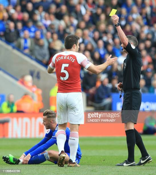 Arsenal's Greek defender Sokratis Papastathopoulos get a yellow card from referee Michael Oliver after fouling Leicester City's English midfielder...