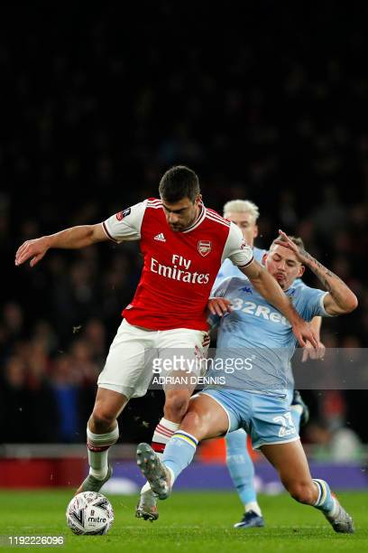 Arsenal's Greek defender Sokratis Papastathopoulos is tackled by Leeds United's English midfielder Kalvin Phillips during the English FA Cup third...